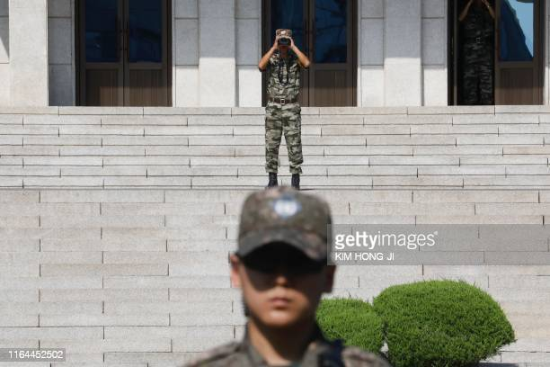 North Korean soldier looks toward the South as a South Korean soldier stands guard at the truce village of Panmunjom inside the Demilitarized Zone...