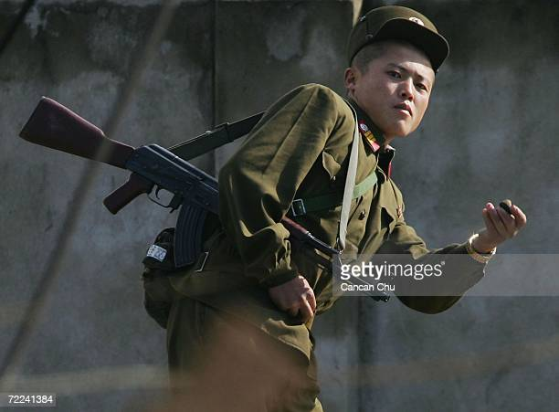 North Korean soldier picks up a stone to throw at photographers on the banks of the Yalu River in the North Korean town of Sinuiju opposite the...