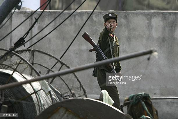 North Korean soldier reacts to be photographed on the banks of the Yalu River in the North Korean town of Sinuiju opposite the Chinese border city of...