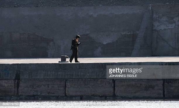 A North Korean soldier reads a book on the banks of the Yalu River at the town of Sinuiju across from the Chinese border town of Dandong on February...