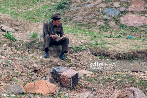 A North Korean soldier reads a book on the banks of the Yalu river near Sinuiju opposite the Chinese border city of Dandong on April 16 2017 Dandong...