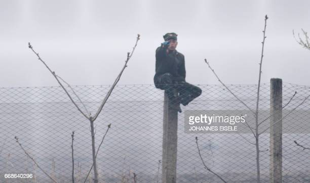 A North Korean soldier sits on a fence near Sinuiju opposite the Chinese border city of Dandong on April 15 2017 China issued a stern warning that a...