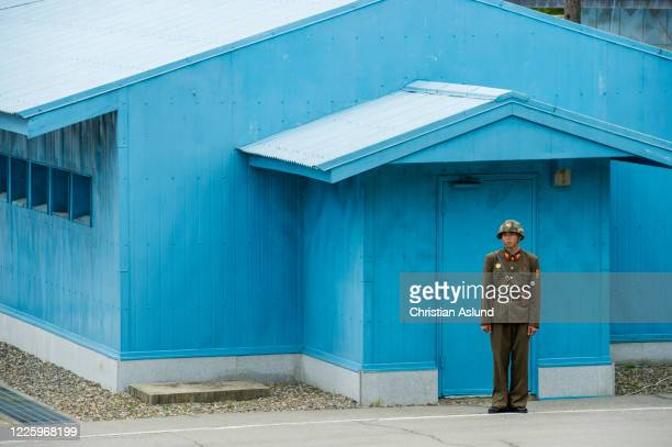 north korean soldier, standing guard at the joint security area (jsa) seen from the north korean side of the military demarcation line (mdl) at panmunjom. the demilitarized zone (dmz) is the border between north and south korea - military demarcation line korea stock pictures, royalty-free photos & images