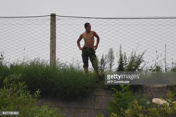 A North Korean soldier stands at a fence on the bank of the Yalu river near the North Korean town of Sinuiju opposite the Chinese border city of...