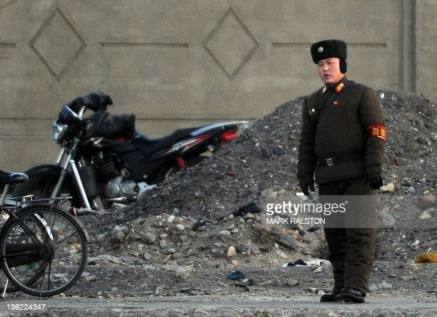 North Korean soldier stands guard beside the Yalu River on the day of the memorial service for the late leader Kim Jong-Il, at the Chinese North...