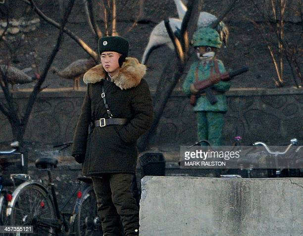 North Korean soldier stands guard on the banks of the Yalu River which separates the North Korean town of Sinuiju from the Chinese border town of...