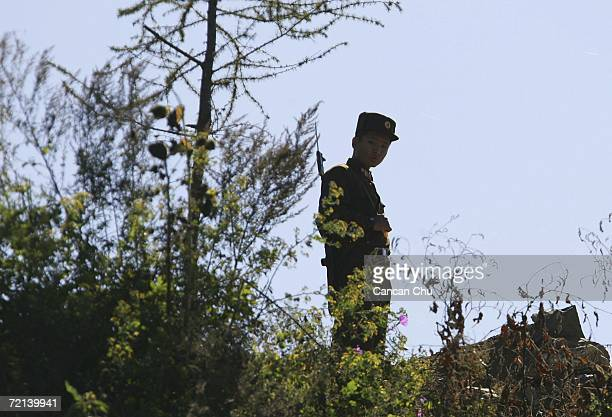 North Korean soldier stands guard on the banks of the Yalu River opposite the Chinese border city of Dandong October 11 2006 in Uiju Democratic...