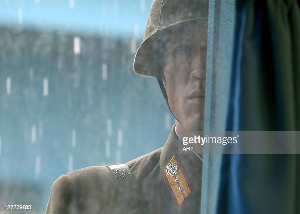 North Korean soldier stands in the rain looking in through a window of a UN truce village building during a visit by US Secretary of State Hillary...