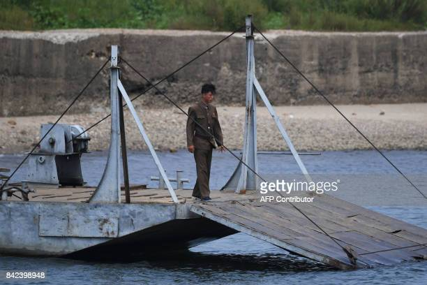 A North Korean soldier stands on a loading ramp on the bank of the Yalu river near the North Korean town of Sinuiju opposite the Chinese border city...