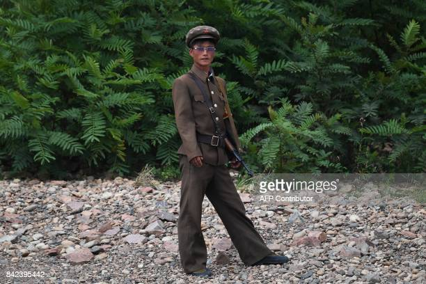 North Korean soldier stands on the bank of the Yalu river near the North Korean town of Sinuiju opposite the Chinese border city of Dandong in...