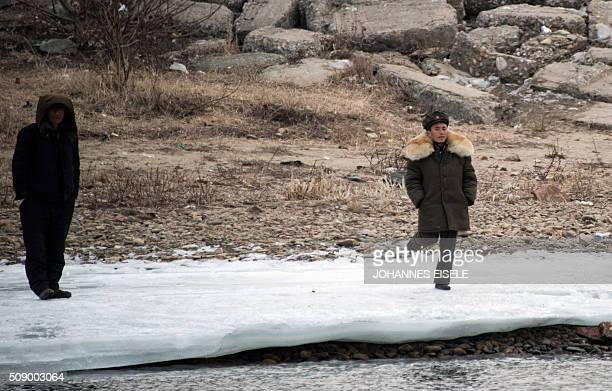 A North Korean soldier stands on the banks of the Yalu River at the town of Sinuiju across from the Chinese border town of Dandong on February 8 2016...