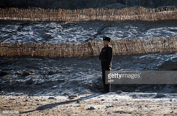 North Korean soldier stands on the banks of the Yalu River at the North Korean town of Sinuiju as seen from across the river from the Chinese border...