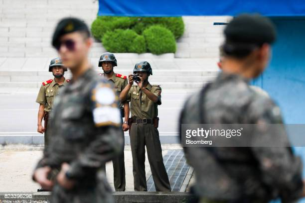 A North Korean soldier takes a photograph as South Korean soldiers stand guard at the truce village of Panmunjom in the Demilitarized Zone in Paju...