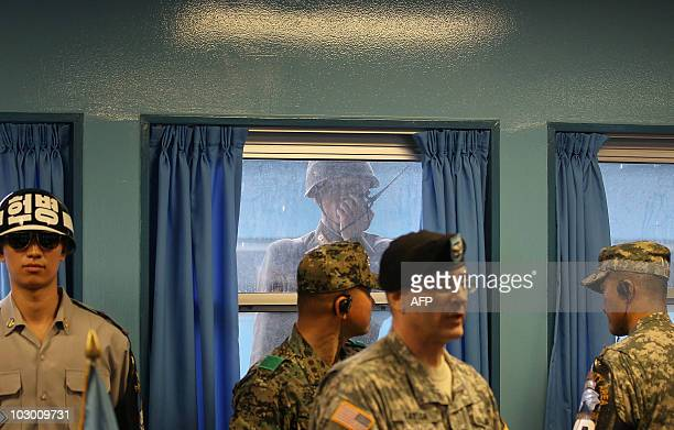 North Korean soldier talks on his walkie-talkie while looking through a window as a South korean soldier stands guard with other military personnel...