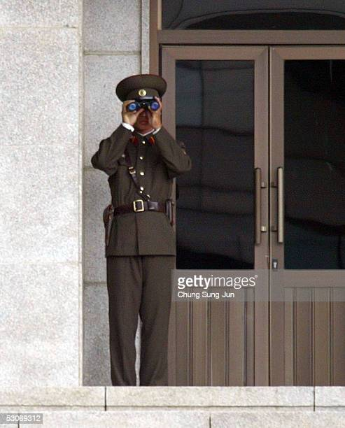 North Korean soldier uses binoculars to look toward South Korea at the border village of Panmunjom between South and North Korea on June 15 2005 in...