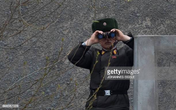 North Korean soldier uses his binoculars to look across the Yalu river near Sinuiju opposite the Chinese border city of Dandong on April 14 2017 A...