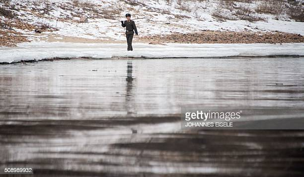 North Korean soldier walks along the banks of the Yalu River in the North Korean town of Sinuiju in an image taken from across the river in the...