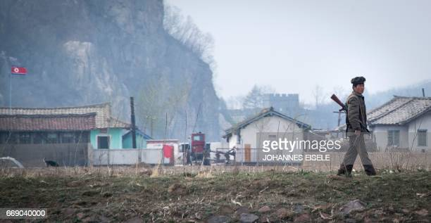 A North Korean soldier walks near the Yalu river near Sinuiju opposite the Chinese border city of Dandong on April 16 2017 Dandong city is the main...