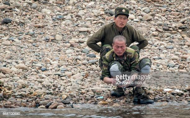 A North Korean soldier washes clothes along the river banks of the Yalu river near Sinuiju opposite the Chinese border city of Dandong on April 15...