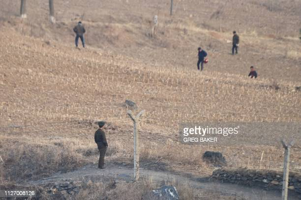 North Korean soldier watches farmers working in a field in North Korea, as seen from a boat on the Yalu river, opposite Hekou, in China's northeast...