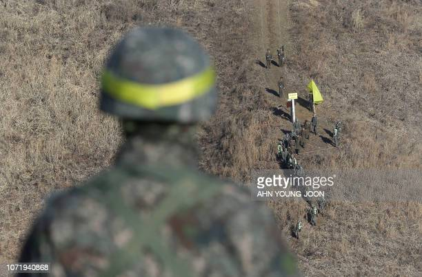 TOPSHOT North Korean soldiers are greeted by South Korean soldiers before crossing the Military Demarcation Line inside the Demilitarized Zone to...