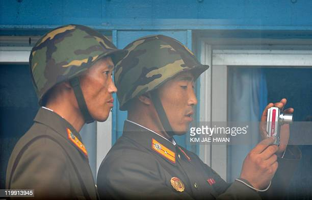 North Korean soldiers are seen through a window from the UN Command Military Armistice Commission meeting room looking at a digital camera at the...