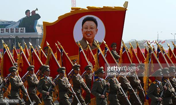North Korean soldiers carry a portrait of late leader Kim JongIl during a military parade to mark 100 years since the birth of the country's founder...