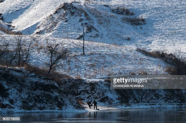 North Korean soldiers collect water from the Yalu river in North Korea's Sakchu county in North Pyongan province as seen from the Chinese border city...