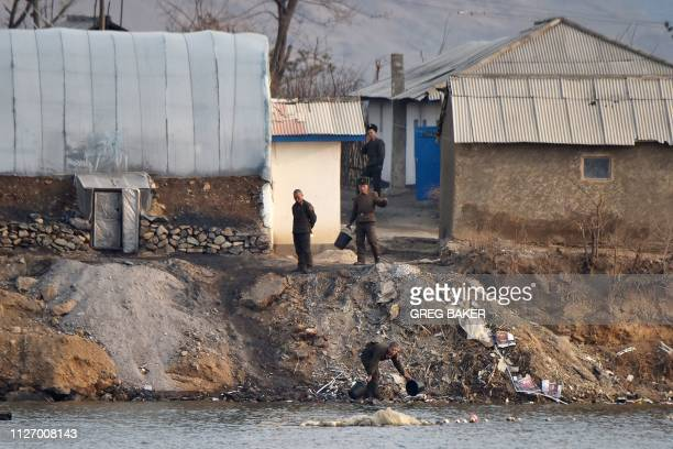 North Korean soldiers collect water outside their barracks on the banks of the Yalu river, as seen from a boat opposite Hekou, in China's northeast...
