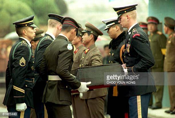 North Korean soldiers hand over remains of US servicemen killed during the Korean War to United Nations honor guards at the Military Demarcation Line...
