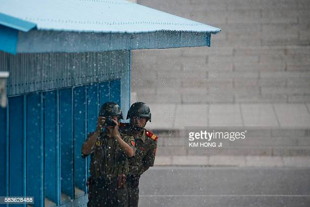 TOPSHOT North Korean soldiers keep watch toward the South side as it rains during a ceremony marking the 63rd anniversary of the signing of the...