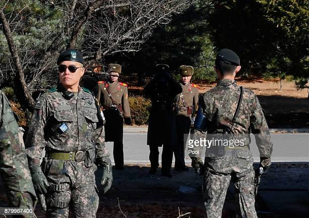North Korean soldiers look at South at a spot where a North Korean defected crossing the border as South Korean Defense Minister Song Youngmoo visit...
