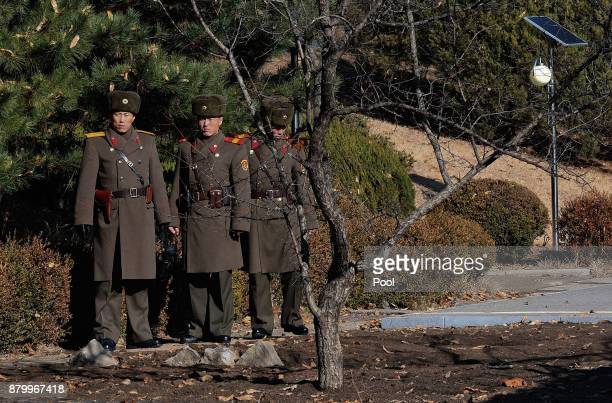 North Korean soldiers look at South next to a spot where a North Korean defected crossing the border as South Korean Defense Minister Song Youngmoo...