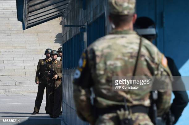 North Korean soldiers look at the South side while US Secretary of Defence Jim Mattis and South Korean Defence Minister Song YoungMoo visit at the...