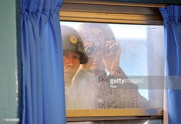 North Korean soldiers look in from outside the UN Command Military Armistice Commission meeting room as newly appointed commander General James...