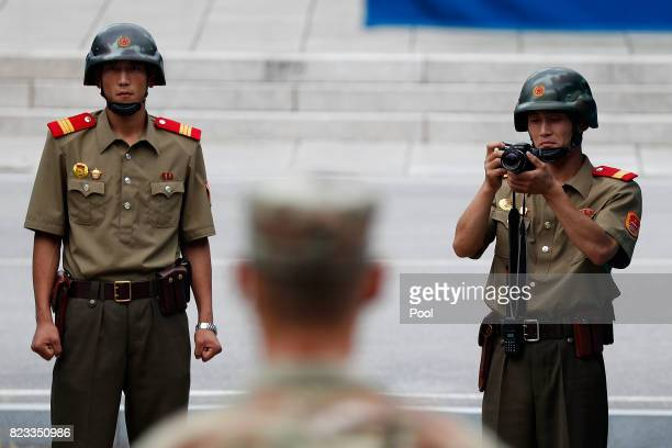North Korean soldiers look on as South Korean and United Nation officials visit after attending a ceremony to commemorate the 64th Anniversary of the...