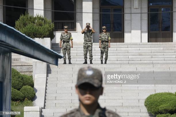North Korean soldiers look toward the South as a South Korean soldier stands guard at the truce village of Panmunjom inside the Demilitarized Zone...
