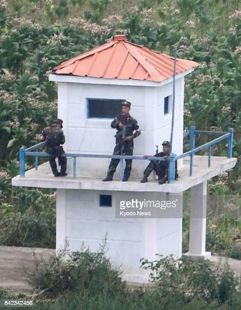 North Korean soldiers on a guard tower near the border are seen from the Chinese city of Tumen in the Yanbian Korean Autonomous Prefecture...
