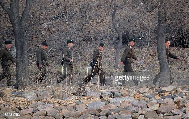 North Korean soldiers patrol along the bank of the Yalu River in the North Korean town of Sinuiju across from the Chinese city of Dandong on April 4...