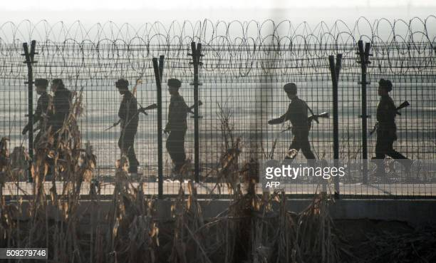 TOPSHOT North Korean soldiers patrol next to the border fence near the town of Sinuiju across from the Chinese border town of Dandong on February 10...