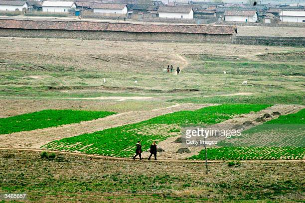 North Korean soldiers patrol the border to China while farmers walk back to their village after an encounter with Chinese boatsmen at a border...