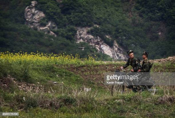 North Korean soldiers ride on a bicycle on the Yalu river north of the border city of Sinuiju North Korea across from Dandong Liaoning province...