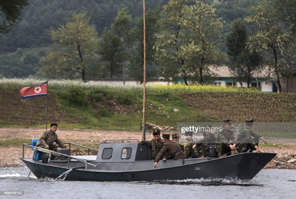 North Korean soldiers ride on a boat used as a local ferry as they cross the Yalu river north of the border city of Dandong, Liaoning province, northern China near Sinuiju, North Korea on May 23, 2017 in Dandong, China. China has long been North Korea's main ally and trading partner, but relations are increasingly strained by continued missile testing and provocations by the regime of Kim Jong Un. The North is almost entirely dependent on trade with China to feeds its impoverished economy, yet it has ignored calls by the international community to halt its nuclear and ballistic missile weapons programs. At least three-quarters of trade between the two nations flows through points along its 880-mile long shared border, a divide that reveals stark contrasts in development. Cities such as Dandong boast high-rise buildings and advanced infrastructure, and the Friendship Bridge serves as the conduit for the bulk of trade. From hired boats along the Yalu river, Chinese tourists peer into the reclusive North, marked by soldiers, meagre villages, and depleted farmland. The United States has pressured China to do more to leverage its clout with North Korea, though Beijing remains concerned that outright regime collapse in Pyongyang could trigger a rush of refugees across the border.