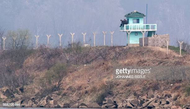 North Korean soldiers sit in a watch tower near Sinuiju opposite the Chinese border city of Dandong on April 15 2017 / AFP PHOTO / Johannes EISELE