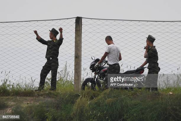 North Korean soldiers stand at a fence on the bank of the Yalu river near the North Korean town of Sinuiju opposite the Chinese border city of...