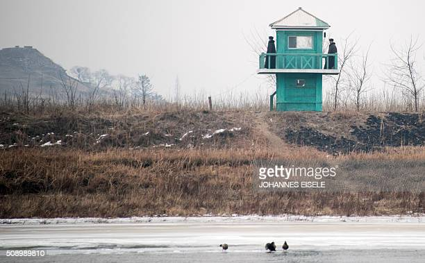 North Korean soldiers stand at their watchtower on the banks of the Yalu River in the North Korean town of Sinuiju in an image taken from across the...