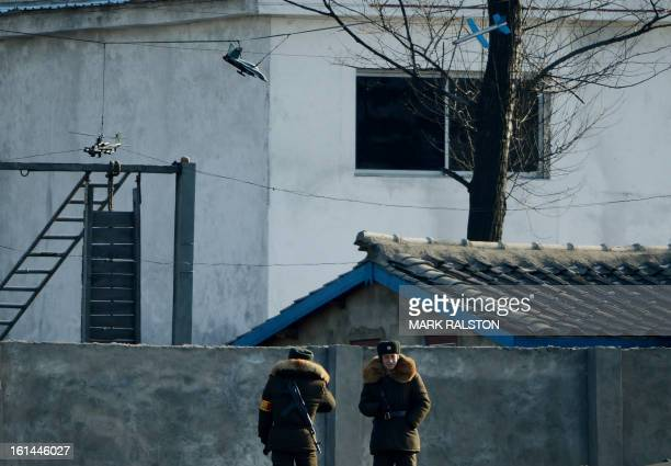 North Korean soldiers stand beneath models of helicopter gunships jets and cruise missiles at their barracks on the banks of the Yalu River at the...