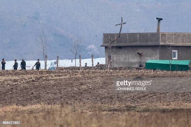 North Korean soldiers stand next to the Yalu river near Sinuiju opposite the Chinese border city of Dandong on April 14 2017 A conflict over North...