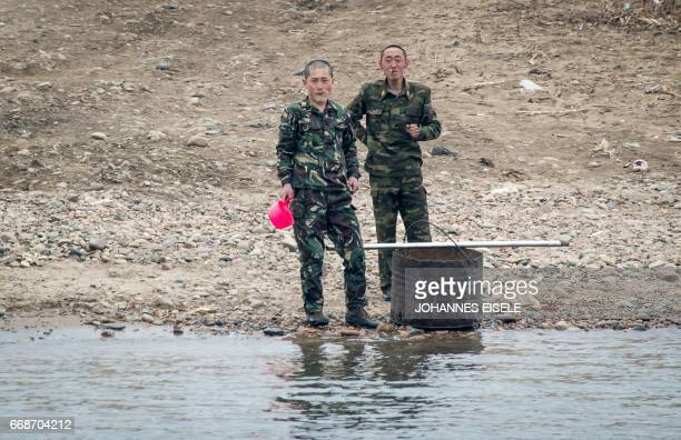 North Korean soldiers stand on the banks of the Yalu river near Sinuiju opposite the Chinese border city of Dandong on April 15 2017 / AFP PHOTO /...
