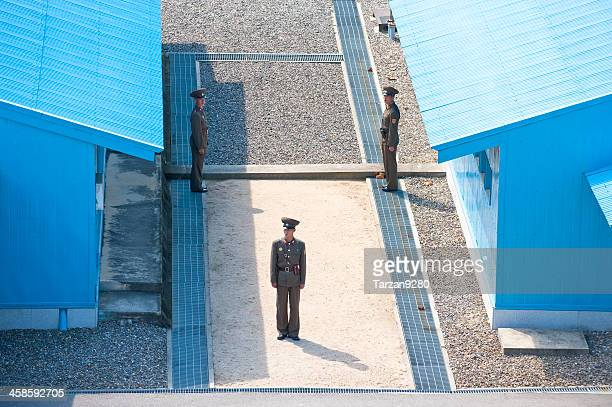 north korean soldiers standing between blue buildings - panmunjom stock pictures, royalty-free photos & images
